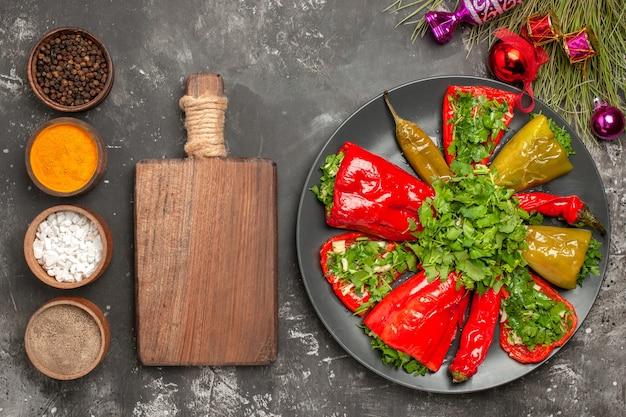 Top vista ravvicinata piatto peperoni sul piatto il tagliere spezie albero di natale giocattoli