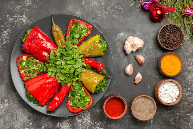 Top close-up vista piatto peperoni sul piatto aglio spezie albero di natale giocattoli