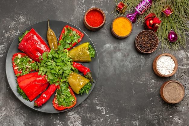 Top vista ravvicinata piatto peperoni con erbe accanto alle ciotole di spezie colorate albero di natale giocattoli