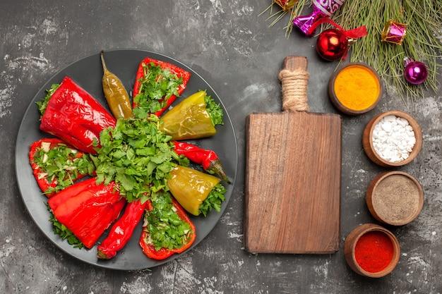 Top vista ravvicinata piatto peperoni con erbe spezie colorate albero di natale giocattoli la tavola di legno