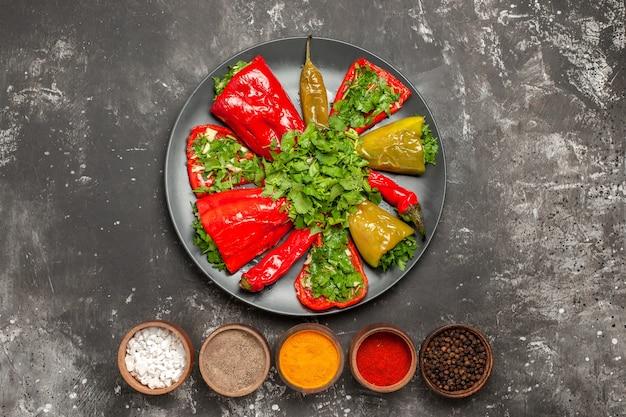 Вид сверху крупным планом блюдо с перцем рядом с мисками разноцветных специй