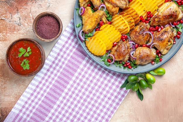Вид сверху крупным планом блюдо соус специи куриные крылышки картофель на бело-фиолетовой скатерти