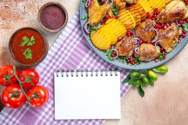 Вид сверху крупным планом блюдо соус специи помидоры курица с картофелем белый блокнот