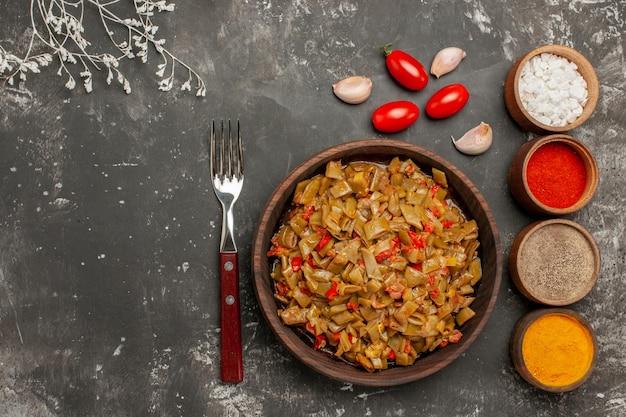 Vista ravvicinata dall'alto piatto e spezie piatto di fagiolini e pomodori forchettano quattro ciotole di spezie colorate e aglio sul tavolo nero