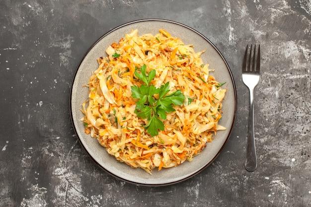 暗い背景にキャベツにんじんハーブフォークの食欲をそそる料理の上部のクローズアップビュー料理