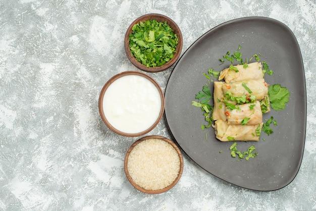 Piatto con vista ravvicinata dall'alto con piatto di erbe di cavolo ripieno accanto a ciotole di riso con panna acida alle erbe su superficie grigia