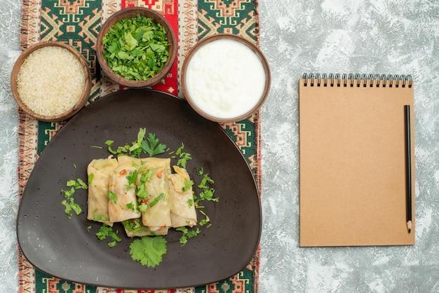 크림 공책과 연필 옆의 테이블 왼쪽에 패턴이 있는 유색 식탁보에 박제 양배추 쌀 허브 사워 크림을 넣은 회색 접시