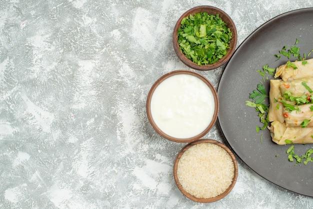 Piatto con vista ravvicinata dall'alto con piatto di erbe di cavolo ripieno accanto a ciotole di panna acida alle erbe e riso sul lato destro del tavolo