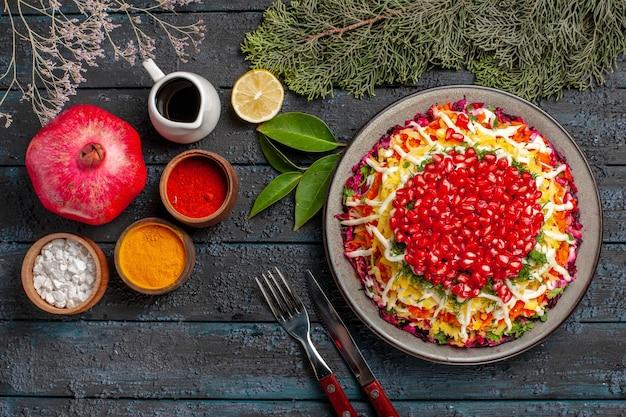 ザクロのトップクローズアップビューザクロザクロレモンカラフルなスパイスナイフとザクロの皿の横にあるフォークスプルースの枝