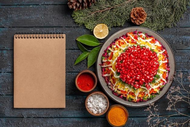 ザクロのスパイスとザクロのレモントウヒの枝とザクロとクリーム色のノートの皿の横にコーンが付いている上部のクローズアップビューの皿