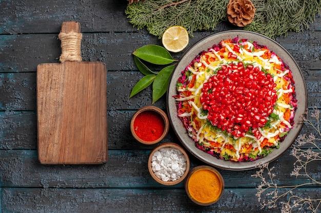 ザクロのスパイスとザクロのレモンのトウヒの枝とザクロと木製のまな板の皿の横にある円錐形の上部のクローズアップビュー皿