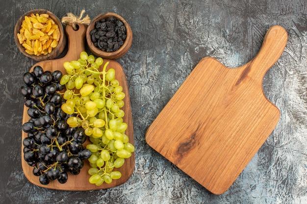 Сверху крупным планом сушеные фрукты, разделочную доску рядом с виноградом и две миски с сухофруктами