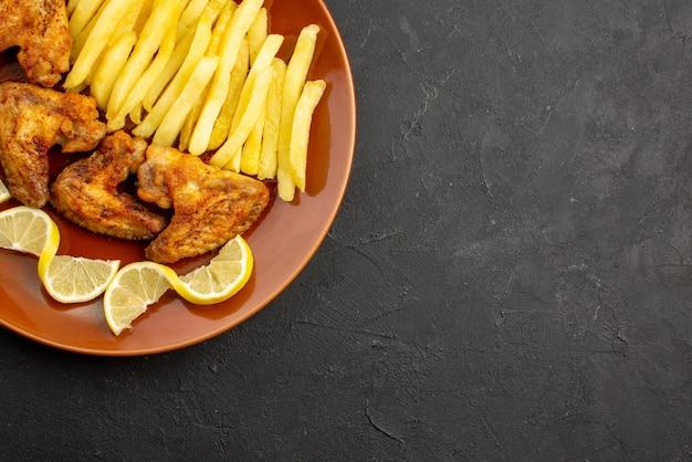 Вид сверху крупным планом фастфуд, аппетитный картофель фри, куриные крылышки и лимон на левой стороне черного стола