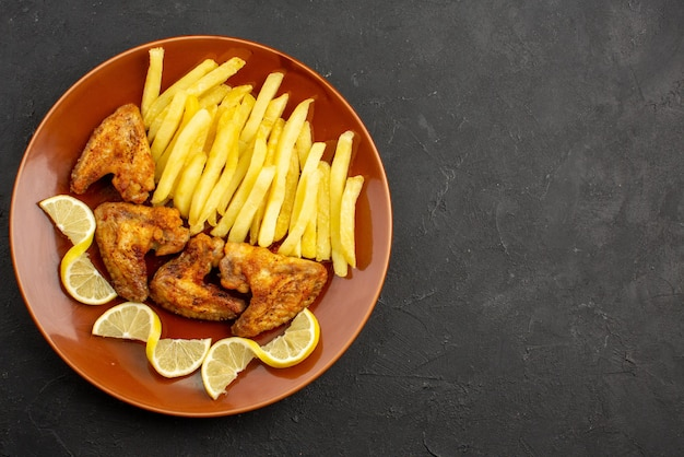 Top close-up view fastfood orange plate of appetizing french fries chicken wings and lemon on the left side of dark table