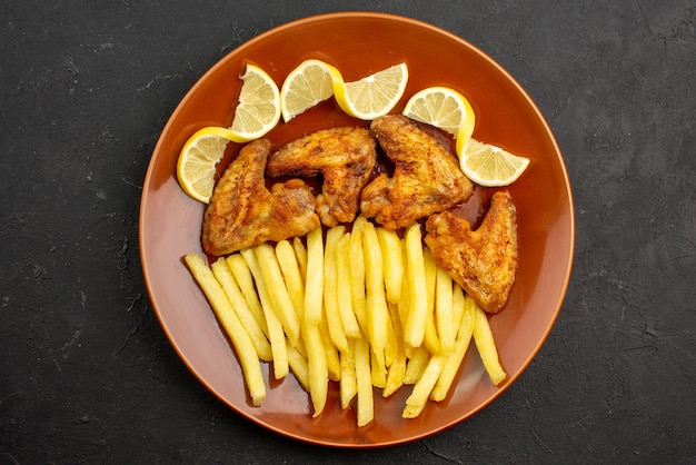 Top close-up view fastfood orange plate of chicken wings with french fries and lemon on the dark table
