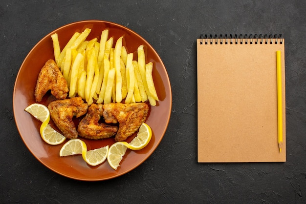 Top close-up view fastfood orange plate of french fries chicken wings and lemon next to the cream notebook and yellow pencil