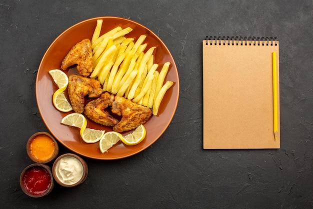 Сверху крупным планом апельсиновая тарелка фастфуда с аппетитными куриными крылышками, картофелем фри и лимоном с тремя видами соусов рядом с блокнотом с кремом и карандашом на темной поверхности