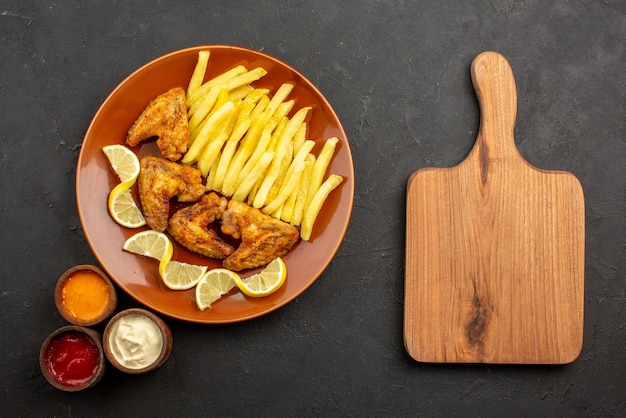 Сверху крупным планом апельсиновая тарелка фастфуда с аппетитными куриными крылышками, картофелем фри и лимоном с тремя видами соусов рядом с разделочной доской на темной поверхности