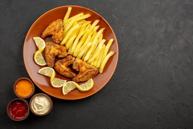 Сверху крупным планом апельсиновая тарелка фастфуда с аппетитными куриными крылышками, картофелем фри и лимоном с тремя видами соусов на левой стороне темного стола