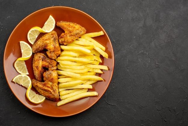 어두운 탁자의 왼쪽에 감자튀김과 레몬이 있는 닭 날개의 클로즈업 보기 패스트푸드 오렌지 플레이트