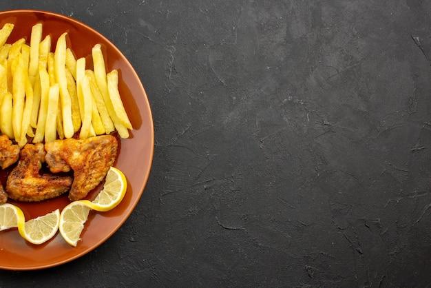 Вид сверху крупным планом фастфуд оранжевая тарелка с картофелем фри, куриными крылышками и лимоном на левой стороне темного стола