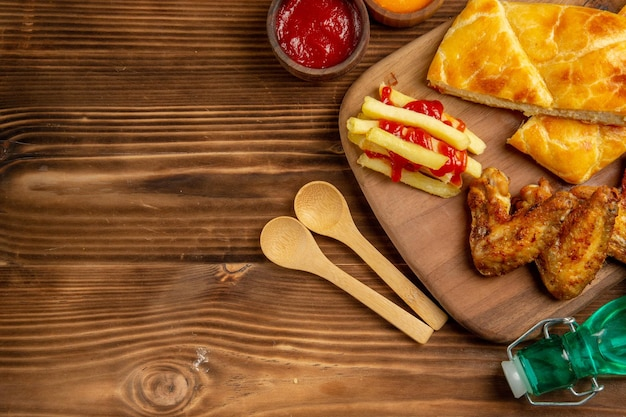 Top close-up view fastfood pie and chicken wings french fries with ketchup on the kitchen board next to the bowls of colorful spices and sauces wooden spoons herbs and bottle