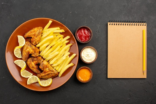Top close-up view fastfood plate of chicken wings french fries and lemon next to bowls of three types of sauces and notebook with pencil on the table