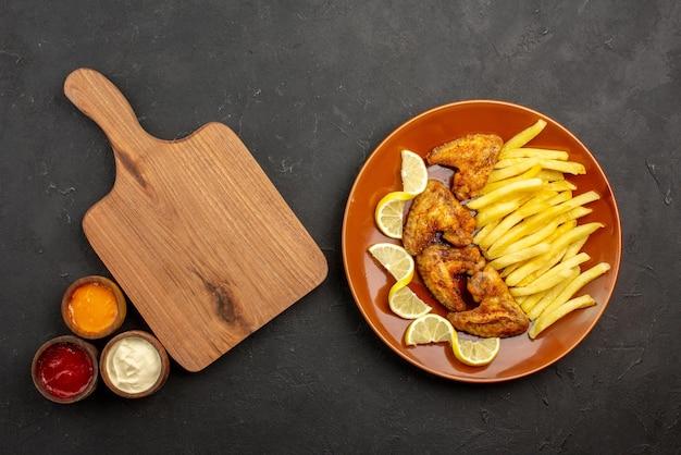 Сверху крупным планом тарелка фастфуда с аппетитными куриными крылышками, картофелем фри и лимоном справа и тремя видами соусов рядом с разделочной доской с левой стороны
