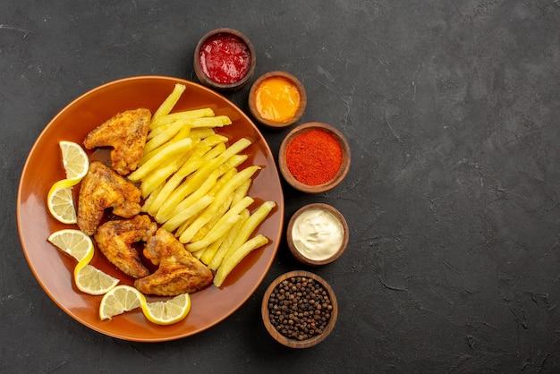 Сверху крупным планом тарелка фастфуда с куриными крылышками, картофелем фри и лимоном, а также тарелки с тремя видами соусов, черного перца и специй на левой стороне стола