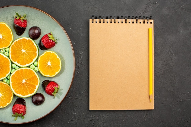 上部の拡大図果物とチョコレートのみじん切りオレンジとチョコレートで覆われたイチゴと緑のキャンディークリームノートブックと黒いテーブルの上の黄色い鉛筆の横にある