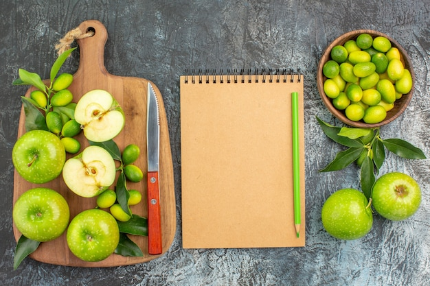 Top close-up view fruits the appetizing apples knife on the board citrus fruits notebook pencil