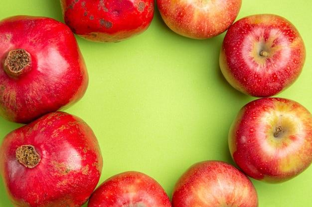 Vista ravvicinata dall'alto, i frutti appetitosi di melograni e mele sono disposti in cerchio