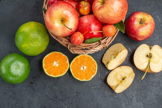 Сверху крупным планом фрукты яблоки и вишни в корзине цитрусовые яблоки