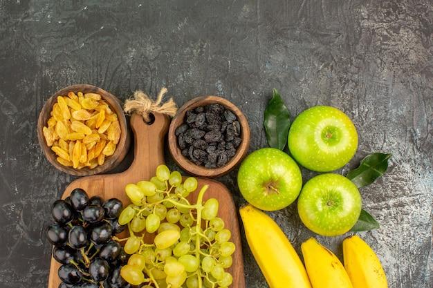 Вид сверху крупным планом фрукты яблоки бананы миски с сухофруктами и виноградом на деревянной доске