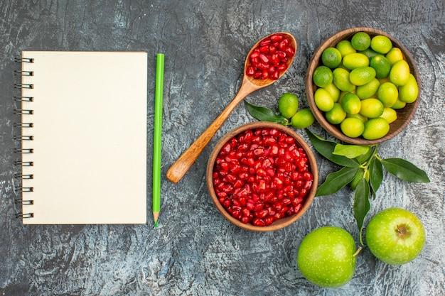 Top vista ravvicinata frutta mele agrumi semi di melograni quaderno a matita