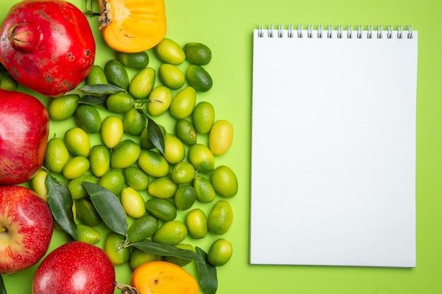 Vista ravvicinata dall'alto frutta mele melograni agrumi cachi e quaderno bianco