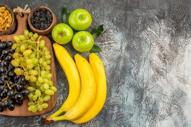Vista ravvicinata dall'alto frutta banane ciotole di frutta secca mele con foglie e uva sul tabellone