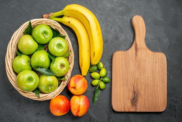 Vista ravvicinata dall'alto frutta banane lime mele nel cesto nettarine accanto al tagliere