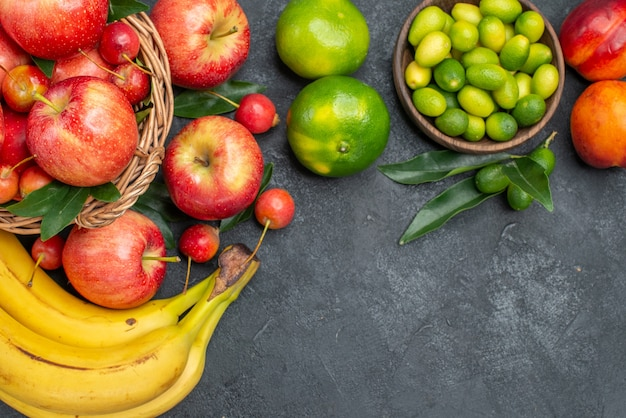 Top vista ravvicinata cesto di frutta di mele ciliegie banane pesche noci agrumi mandarini