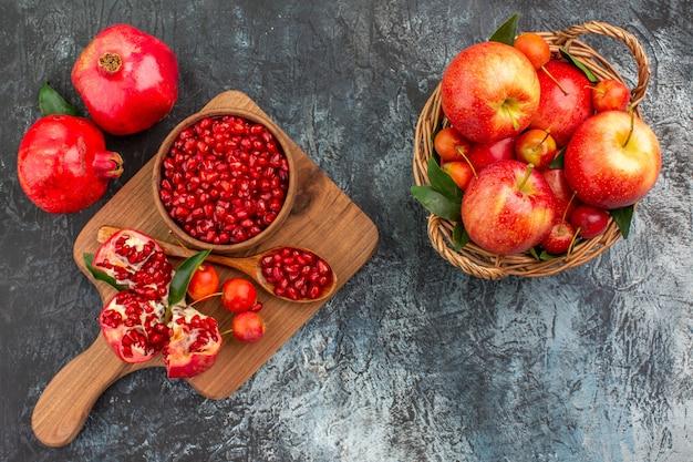Вид сверху крупным планом фрукты, корзина с фруктами, доска с гранатовой ложкой, вишней