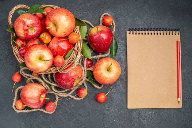 Top close-up view fruits basket with apples cherries next to the fruits and rope notebook pencil