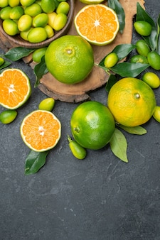 Top close-up view fruits the board of different kinds citrus fruits on the dark table
