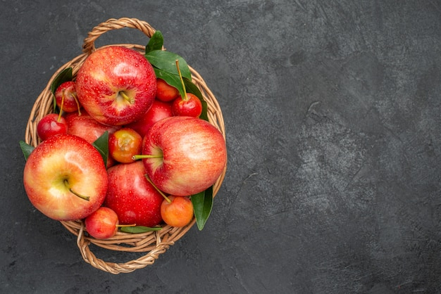 暗いテーブルのバスケットの上のクローズアップビューフルーツチェリーとリンゴ
