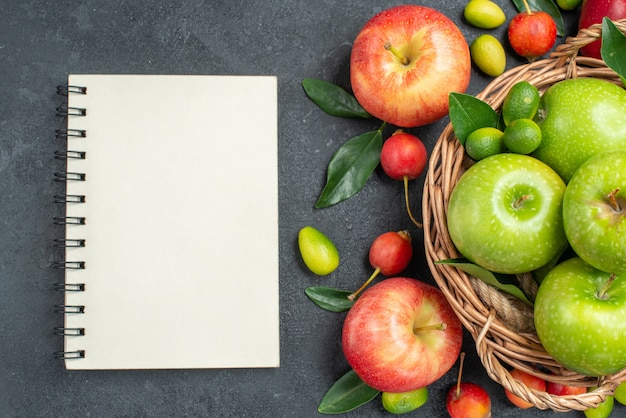 Top vista ravvicinata frutti ciliegie mele cesto di mele verdi con foglie notebook bianco