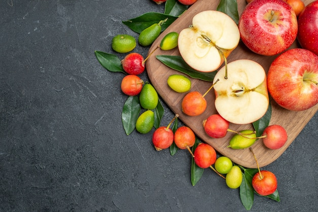 Top close-up view fruits cherries apples with leaves citrus fruits on the cutting board