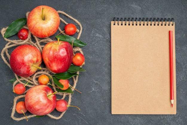 上のクローズアップビューフルーツチェリーロープ赤黄色のリンゴの葉ノート鉛筆