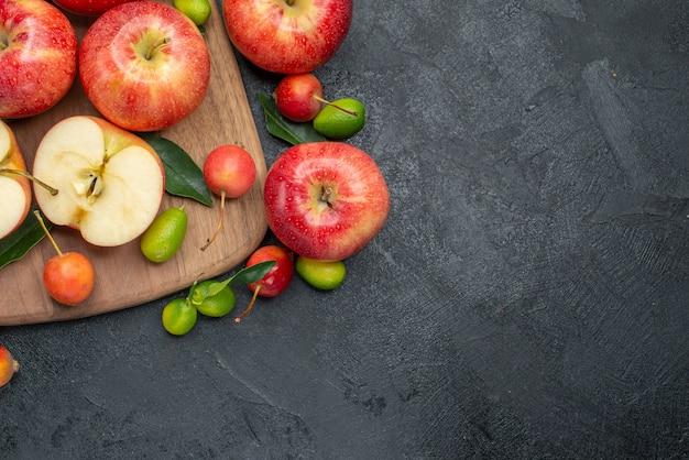 Вид сверху крупным планом фрукты цитрусовые рядом с фруктами и ягодами на доске