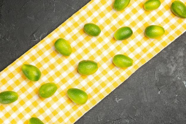 어두운 탁자에 있는 체크무늬 식탁보에 있는 과일 감귤류 과일