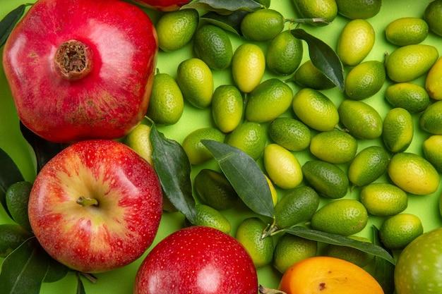 상위 클로즈업 보기 과일 감귤류 과일 석류 사과 녹색 테이블에