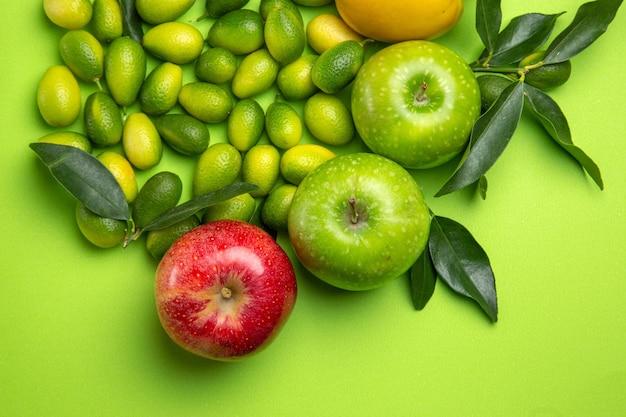 上のクローズアップビューフルーツカラフルなリンゴ柿柑橘系の果物と緑のテーブルの葉